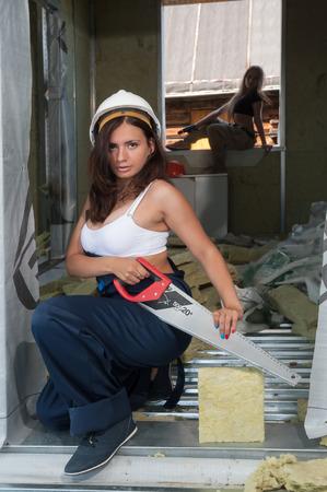 serrucho: trabajador de la construcción mujer en casco con sierra de mano
