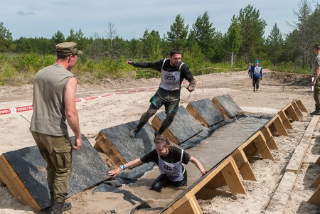 carry out: Tyumen, Russia - June 11, 2016: Race of Heroes project on the ground of the highest military and engineering school. Participants carry out anti-gravitation exercise. The girl has fallen in water