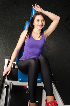 exersice: Cute young brunette making exersice on simulator at the gym