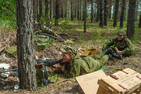 ambush: Tyumen, Russia - June 11, 2016: Race of Heroes project on the ground of the highest military and engineering school. Machine gunners ambush in forest Editorial