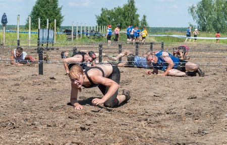 barbed wires: Tyumen, Russia - July 9, 2016: Steel Character extrim race on Voronino Hill. Army Test. People jumping, crawling,passing under a barbed wires or climbing obstacles during extreme obstacle race