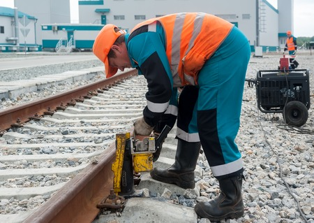 establishes: Tobolsk, Russia - July 15. 2016: Sibur company. The worker establishes a hydraulic jack for lifting rails for the purpose of repair of a railroad body