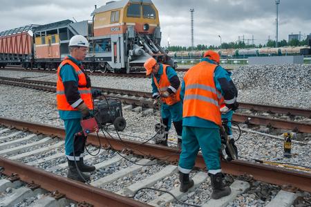 rail cross: Tobolsk, Russia - July 15. 2016: Sibur company. Railway workers repairing railway