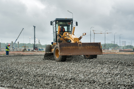 grader: Tobolsk, Russia - July 15. 2016: Sibur company. Construction of plant on processing of hydrocarbonic raw materials. Grader leveling gravel on construction site in rainy weather Editorial