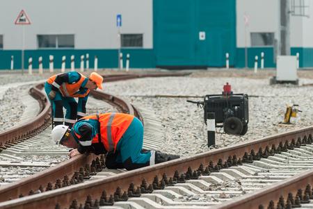 Tobolsk, Russia - July 15. 2016: Sibur company. Denisovka railway station. Railway workers repairing rail in rainy weather Editorial