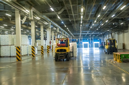 truck driver: Tobolsk, Russia - July 15. 2016: Sibur company. Central control panel of Tobolsk Polymer plant. Driver on forklift truck loads pallets with finished goods from packaging machine to warehouse