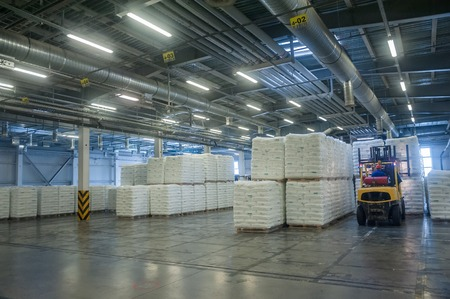 truck driver: Tobolsk, Russia - July 15. 2016: Sibur company. Central control panel of Tobolsk Polymer plant. Driver on forklift truck loads pallets with finished goods from packaging machine