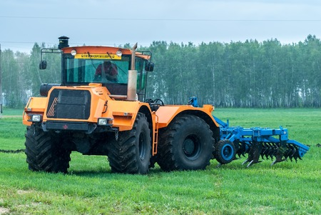 Tyumen, Russia - June 24, 2016: The 5th open championship of Russia on a plowed land. Operator plows the site on Belarus tractor in rainy weather Editorial