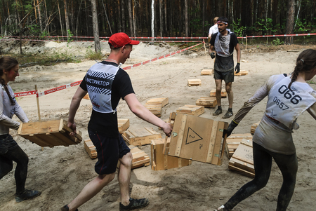 crosscountry: Tyumen, Russia - June 11, 2016: Race of Heroes project on the ground of the highest military and engineering school. Transfer of boxes stage. Athletes bear box with cartridges weighing 28 kilograms