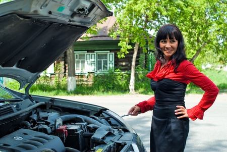 cowl: Attractive smiling business woman near car with an open cowl