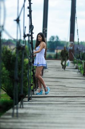 Jolie femme en blanc costume marin debout sur le vieux pont de bois Banque d'images