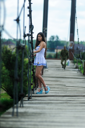 Jolie femme en blanc costume marin debout sur le vieux pont de bois
