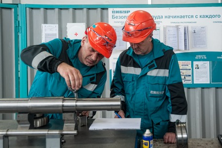 carry out: Tobolsk, Russia - July 15. 2016: Sibur company. Polymer plant. Mechanics carry out adjusting in the shop Editorial