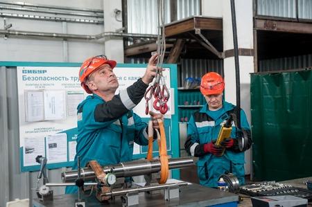 Tobolsk, Russia - July 15. 2016: Sibur company. Polymer plant. Mechanics transfer detail to workbench by crane Editorial