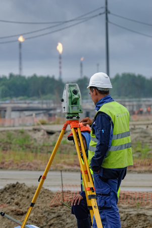 tacheometer: Tobolsk, Russia - July 15. 2016: Sibur company. Construction of plant on processing of hydrocarbons. Surveyor builder worker with theodolite transit equipment at construction site outdoors during surveying work Editorial