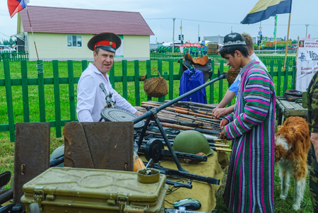cossack: Tyumen, Russia - June 24, 2016: The 5th open championship of Russia on a plowed land. Senior cossack demonstrates rifles collection