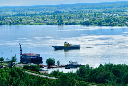 transported: Little ferry is transported through Irtysh river Stock Photo
