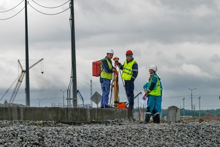 surveying: Tobolsk, Russia - July 15. 2016: Sibur company. Construction of plant on processing of hydrocarbons. Surveyor builders worker with theodolite transit equipment at construction site outdoors during surveying work