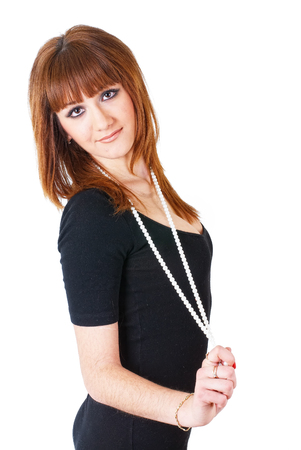 Portrait of attractive young red-haired woman with beads. Isolated over white background photo