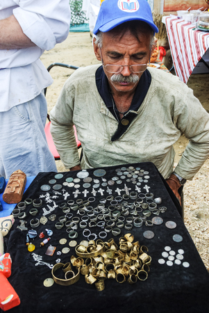 numismatist: Tyumen, Russia - June 24, 2016: The 5th open championship of Russia on a plowed land. Man numismatist shows his collection of coin