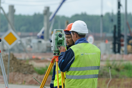 Tobolsk, Russia - July 15. 2016: Sibur company. Construction of plant on processing of hydrocarbons. Surveyor builder worker with theodolite transit equipment at construction site outdoors during surveying work Editorial