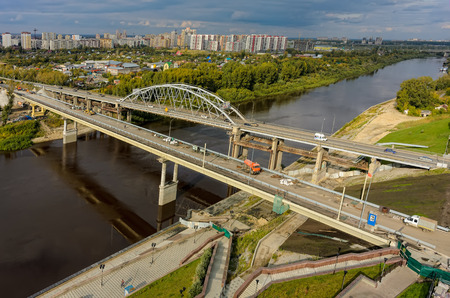 Tyumen, Russia - September 3, 2015: Aerial view of Tura river and bridge on Chelyuskinskaya street. Nearby there is construction of new one. Editorial