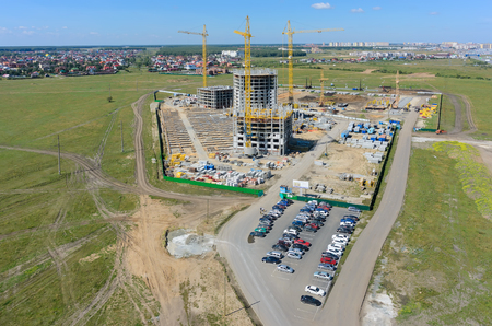 residental: Tyumen, Russia - July 15, 2015: Aerial view on lifting cranes on residental house construction site. Three athletes housing estate