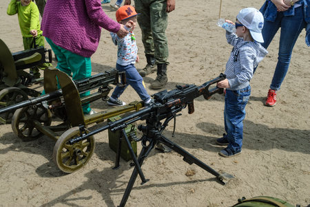 considers: Tyumen, Russia - June 11, 2016: Race of Heroes project on the ground of the highest military and engineering school. Exhibition of weapon. Boy considers an easel machine gun