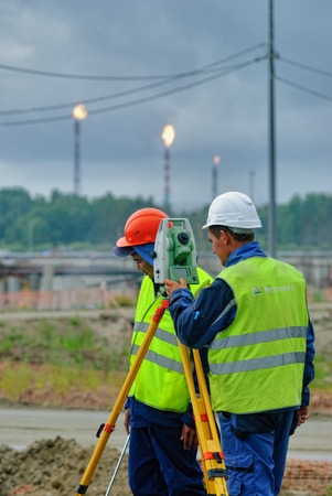 theodolite: Tobolsk, Russia - July 15. 2016: Sibur company. Construction of plant on processing of hydrocarbons. Surveyor builder worker with theodolite transit equipment at construction site outdoors during surveying work Editorial