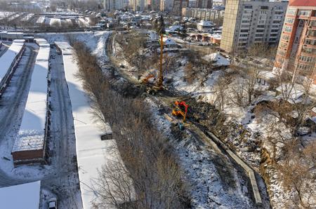 residential tree service: Aerial view onto construction works on strengthening of Tyumenka river bank near Polevaya Street Stock Photo