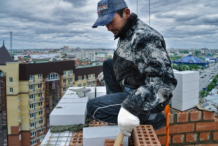 residental: Tyumen, Russia - May 23, 2008: Construction of 18 floor brick residental house at intersection of streets of Gercena and Chelyuskincev. Bricklayer behind works on 18th floor Editorial