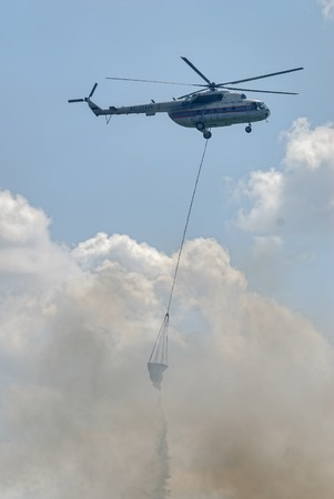 fire extinguishing: Nizhniy Tagil, Russia - July 12. 2008: MI-8 helicopter of Emergency situations Ministry flies with water tank for fire extinguishing