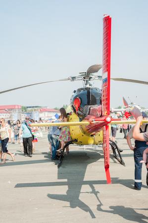 Tyumen, Russie - 11 Août, 2012: Spectacle aérien Lors d'une visite à UTair en héliport Plehanovo. Les gens explorent Eurocopter AS-355NP Ecureuil 2
