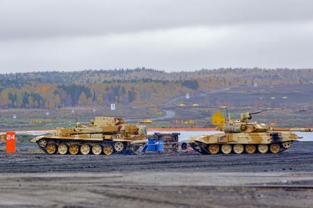 armoured: Nizhniy Tagil, Russia - September 27. 2013: Armoured recovery vehicle BREM-1M evacuates t-90S tank on exhibition range. RAE-2013 exhibition