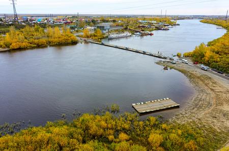 water bus: Tyumen, Russia - September 26, 2015: Bird eye view onto traffic through pontoon bridge over Tura river. Russian text on ship board - Tyumen college of water transport