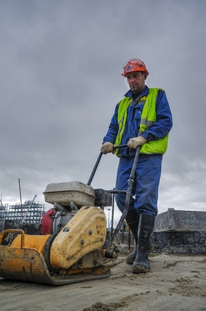 compaction: Tobolsk, Russia - July 15. 2016: Sibur company. Construction of plant on processing of hydrocarbonic raw materials. Builder worker at sand ground compaction with vibration plate compactor machine
