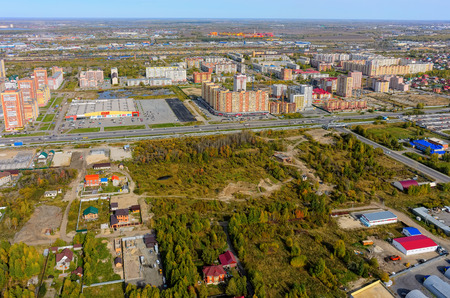 okey: Tyumen, Russia - September 16, 2015: Okey shopping mall of household goods with a lot of parking space, East-2 residential district. Aerial view. Autumn