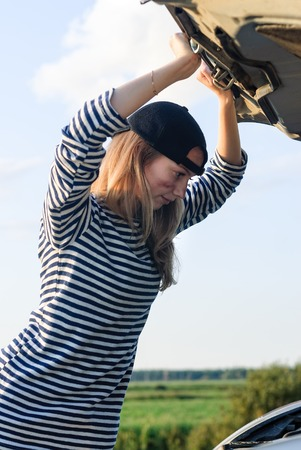 young blond girl with broken down car with hood open photo