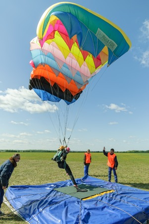Yalutorovsk, Russia - May 24, 2008: Competition of parachutists on landing accuracy on sport airdrome. Paratrooper woman descends