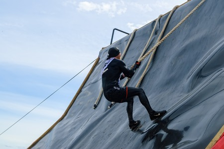Tyumen, Russia - June 11, 2016: Race of Heroes project on the ground of the highest military and engineering school. High wall stage. Sportsman storms wall Editorial