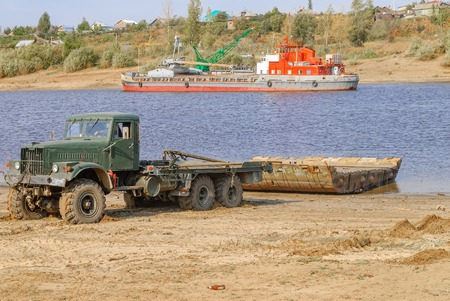 Tyumen, Russia - September 19, 2009: Truck is pulling module of pontoon bridge from Tura river