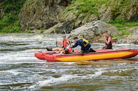 Beklenischevo, Russia - June 12, 2005: Four water tourists move on rapid river. The girl fell in water