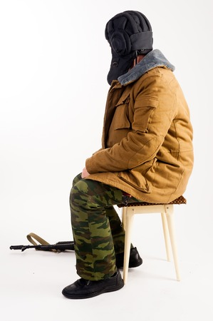 The officer-tankman with the AKM assault rifle sits on a stool. Isolated over white background Stock Photo
