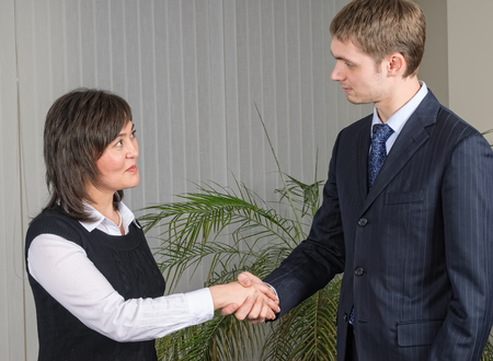 Handshake of business partners, men and women in the office photo