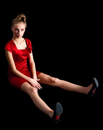 Young fashionable model in red dress sits on floor. Isolated over black background photo