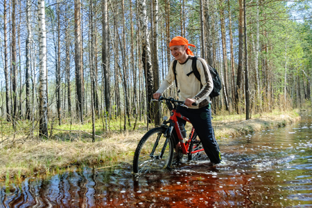 Man on bicycle goes along road flooded