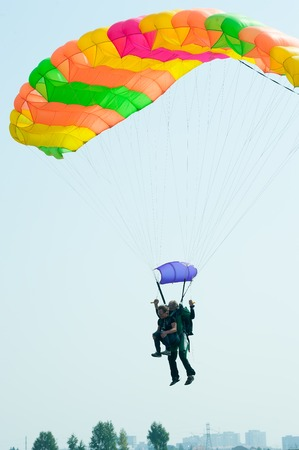 Tyumen, Russia - August 11, 2012: Air show On a visit at UTair in heliport Plehanovo. Parachute jump in tandem in show program Editorial