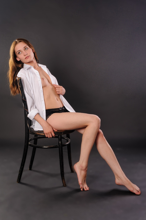 Young beautiful woman in open shirt with open breast sitting on chair photo