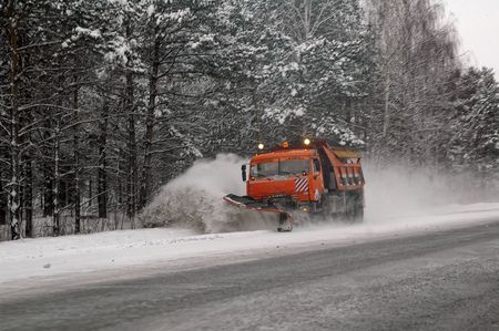 tree removal service: Tyumen, Russia - December 2, 2006: Snowplow removing snow from intercity road from snow blizzard