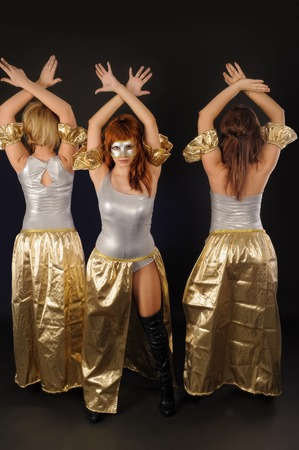 Trio of young beautiful women in dancing costumes over black background photo